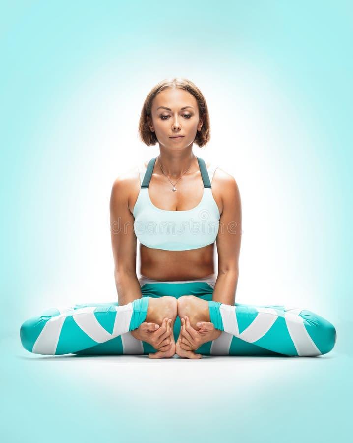 Йога атлетической молодой женщины практикуя на предпосылке бирюзы Mulabandhasana стоковые изображения rf