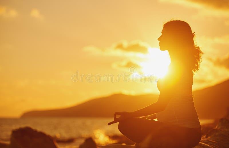 Йога беременной женщины практикуя в положении лотоса на пляже на солнце стоковое фото rf