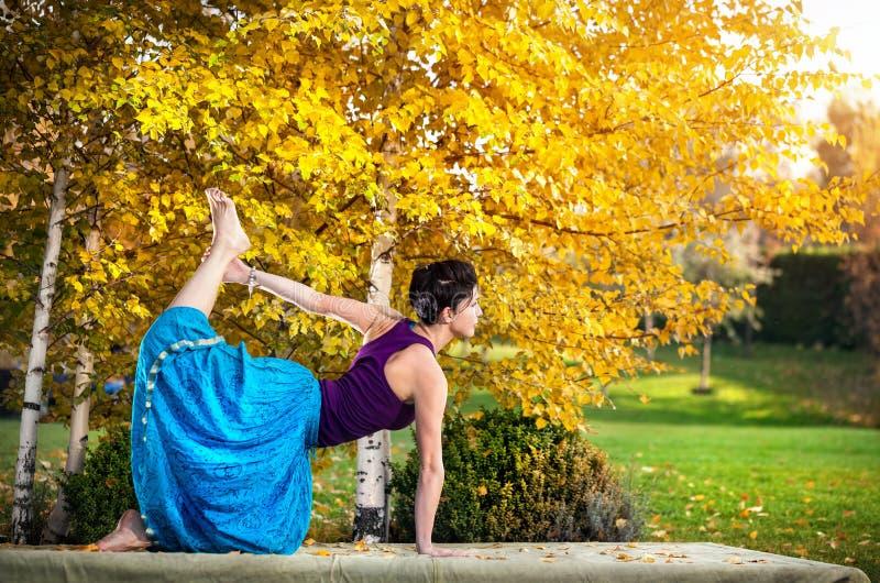 Йога в парке осени стоковые фотографии rf
