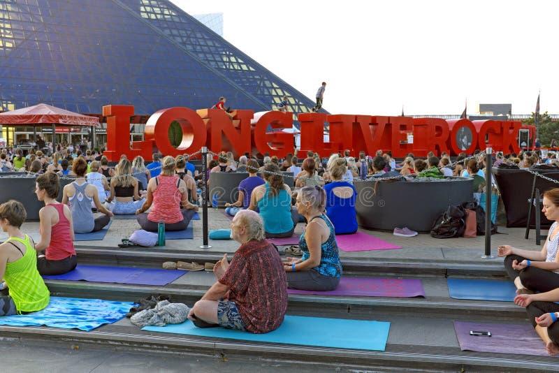 Йога группы на площади вне мемориала рок-н-ролла в Кливленд, Огайо, США стоковое фото
