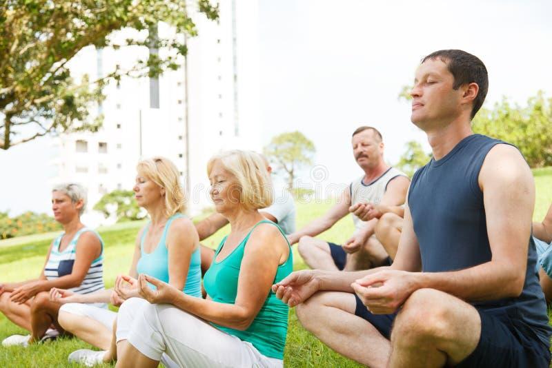 Йога группы людей практикуя стоковые фото