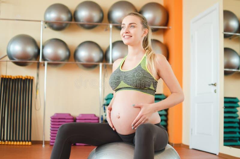 Йога для беременных женщин Молодая беременная девушка делая йогу стоковые изображения