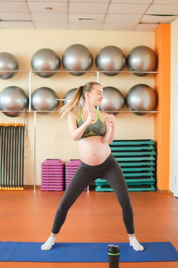 Йога для беременных женщин Молодая беременная девушка делая йогу стоковое изображение