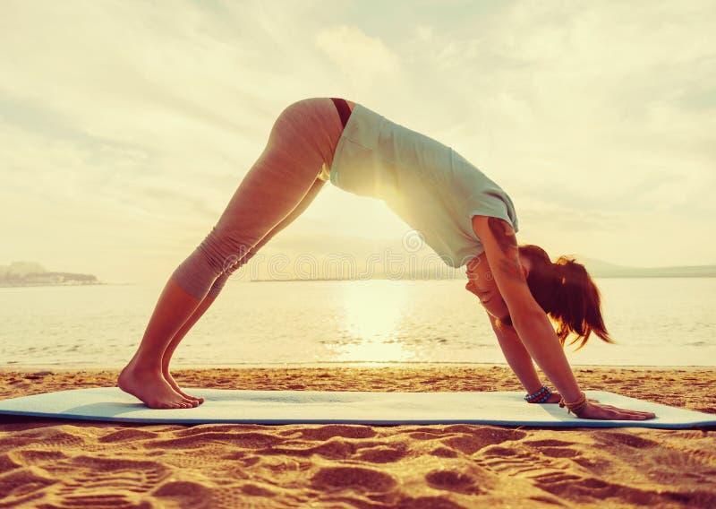 Йога девушки практикуя на пляже стоковое фото