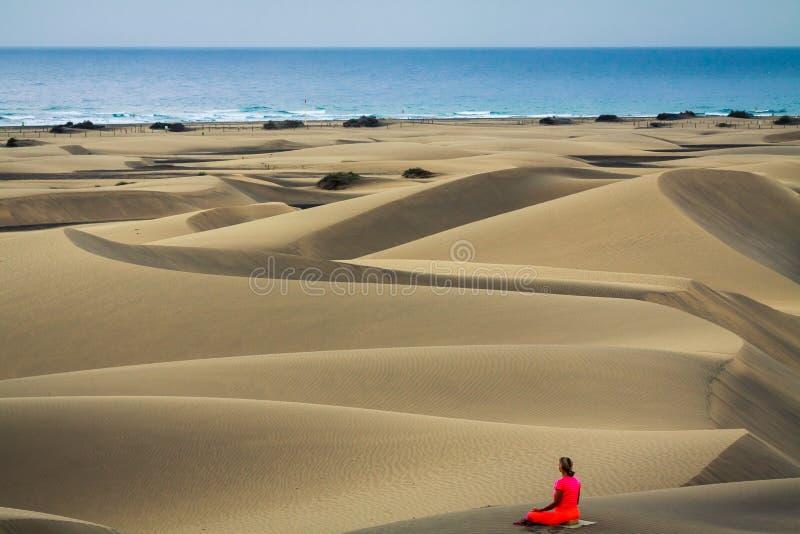 Йога женщины практикуя в песчанных дюнах стоковые изображения