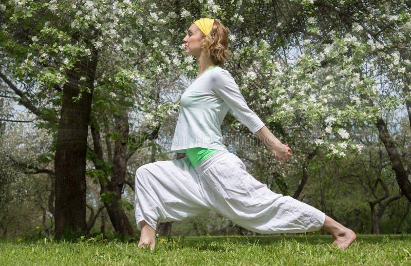 Йога женщины практикуя в саде против детенышей весны цветка принципиальной схемы предпосылки белых желтых стоковое изображение