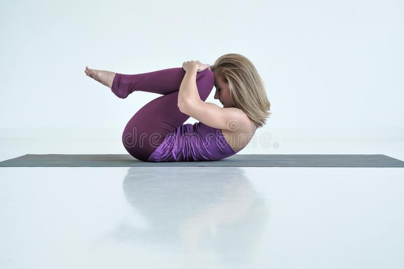 Йога женщины практикуя, делая колени к тренировке комода, представление Apanasana стоковое изображение