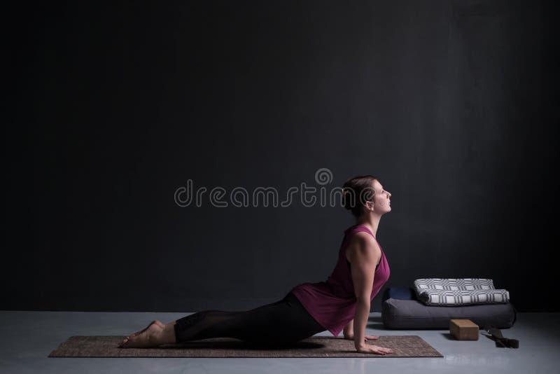 Йога женщины практикуя, делая svanasana mukha urdhva, вверх смотря на представление собаки стоковые фотографии rf