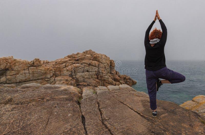 Йога женщины практикуя на побережье панцыря стоковые фотографии rf