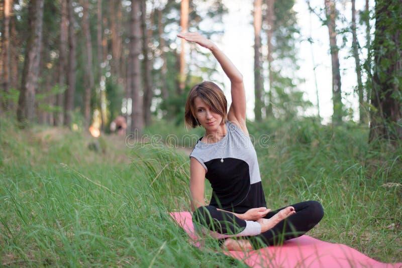 Йога женщины практикуя самостоятельно в парке на открытом воздухе стоковое фото