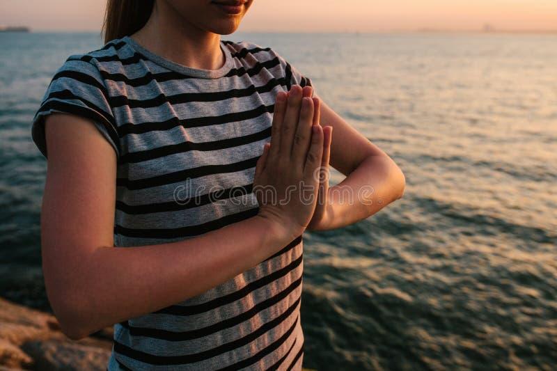 Йога и раздумье молодой красивой девушки практикуя на утесах рядом с морем на заходе солнца Спорт йога раздумье стоковое изображение