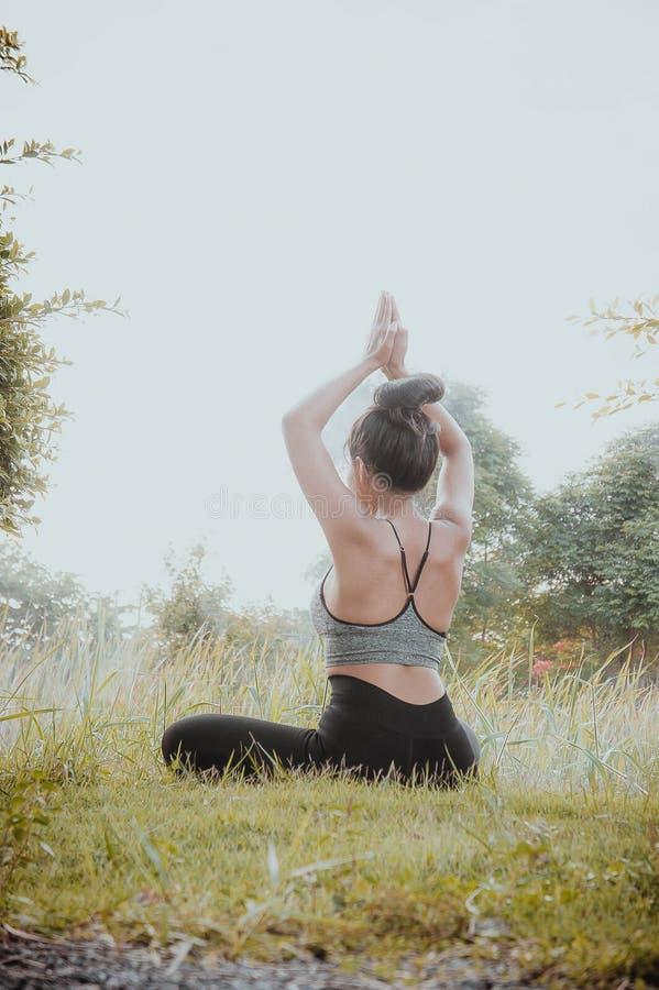 Йога йоги молодой женщины практикуя ежедневная помогает в концентрации стоковые фото
