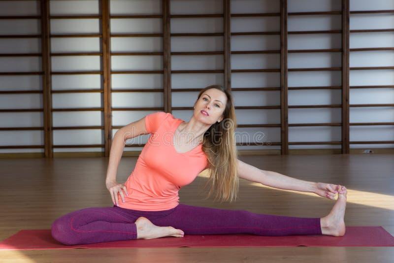 Йога красивой женщины практикуя внутри помещения стоковые изображения