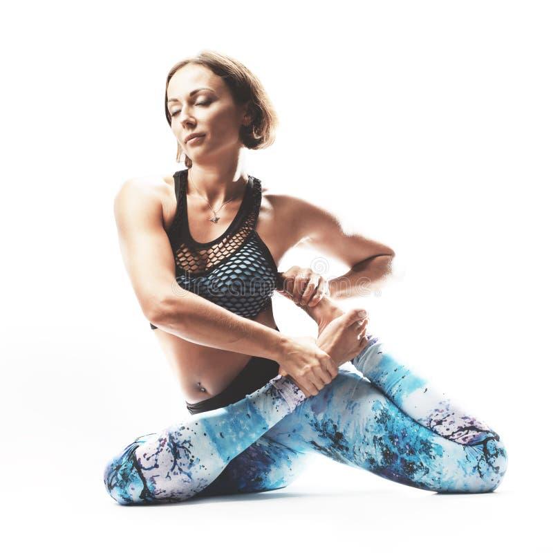 Йога красивой молодой женщины практикуя на белой предпосылке стоковые изображения rf