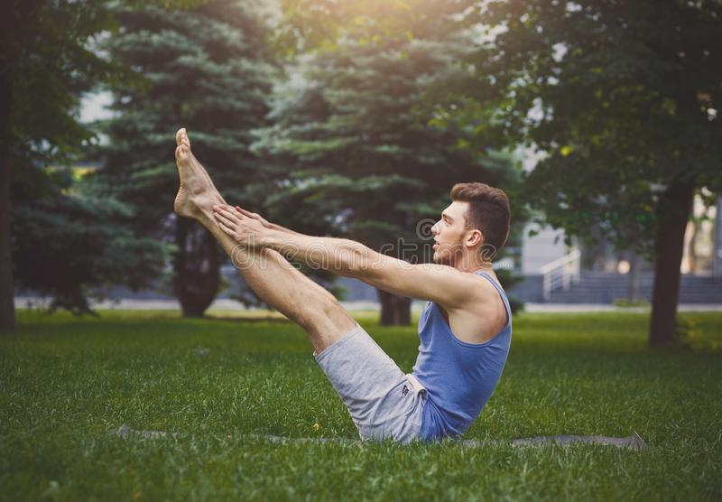 Йога молодого человека практикуя в представлении шлюпки outdoors стоковые изображения rf