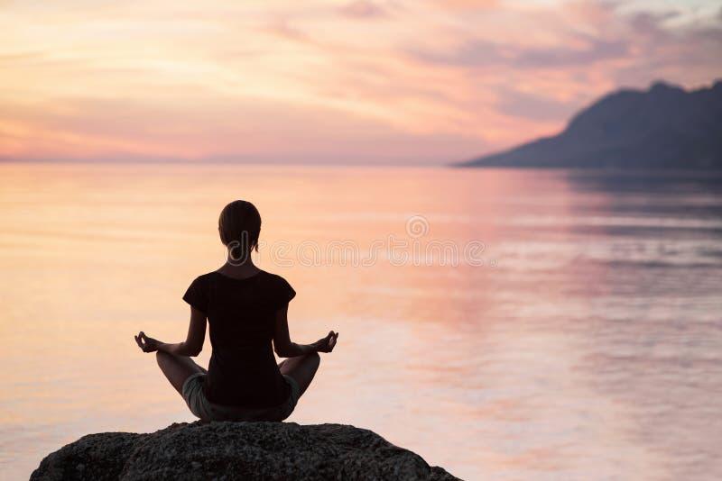 Йога молодой женщины практикуя около моря на заходе солнца Сработанность, раздумье и концепция перемещения Здоровый уклад жизни стоковые фото