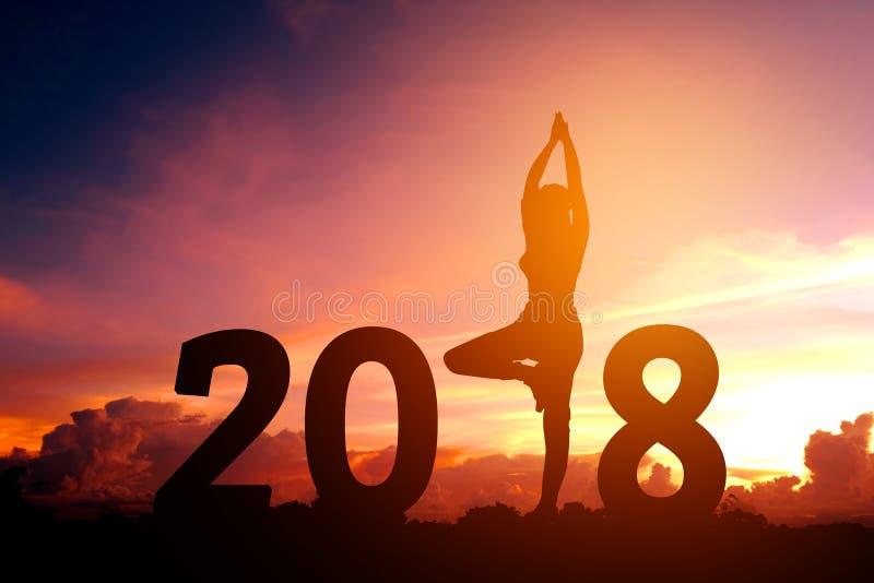 Йога молодой женщины силуэта практикуя на 2018 Новых Годах стоковое изображение rf
