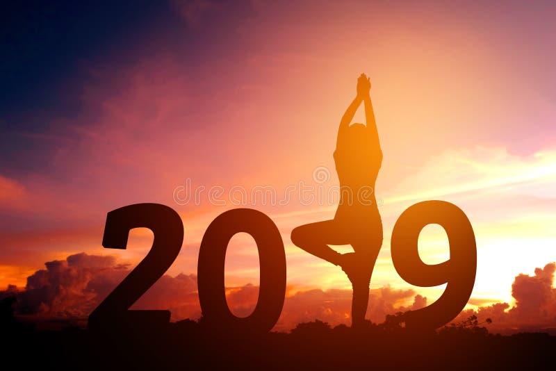 Йога молодой женщины силуэта практикуя на 2019 Новых Годах стоковое изображение