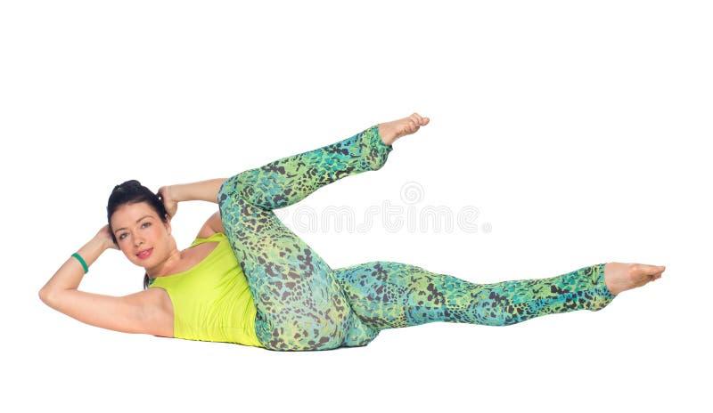 Йога молодой женщины практикуя, лежа дальше подпирает с ногами вверх по variatio стоковое фото rf