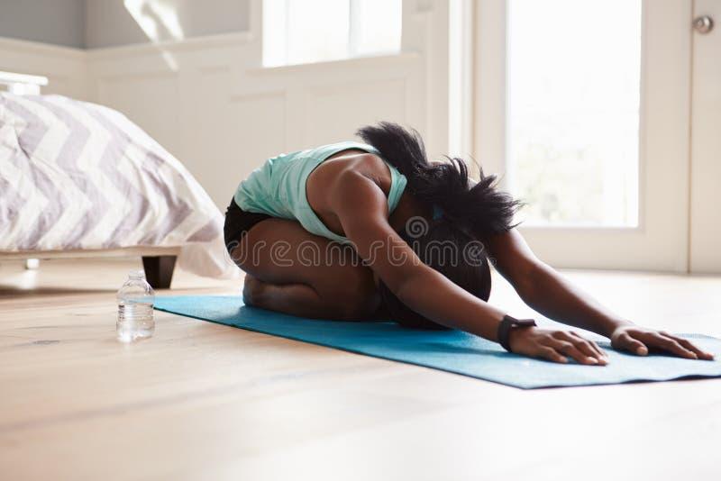 Йога молодой чернокожей женщины практикуя в представлении простирания кота стоковые изображения