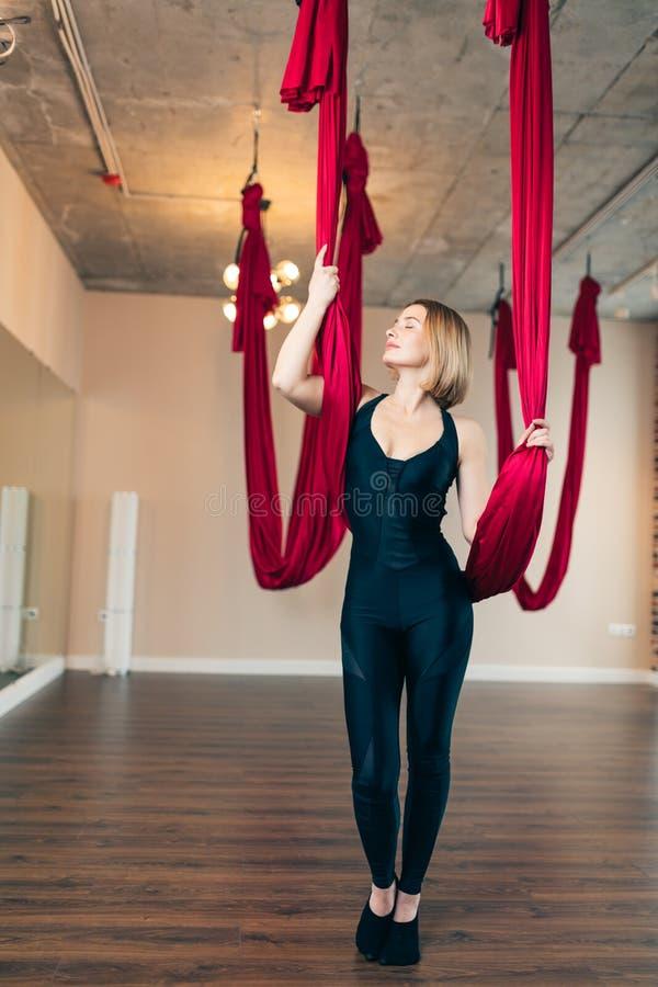 Йога мухы Девушка сидя в красном гамаке для антигравитационной воздушной йоги стоковое изображение