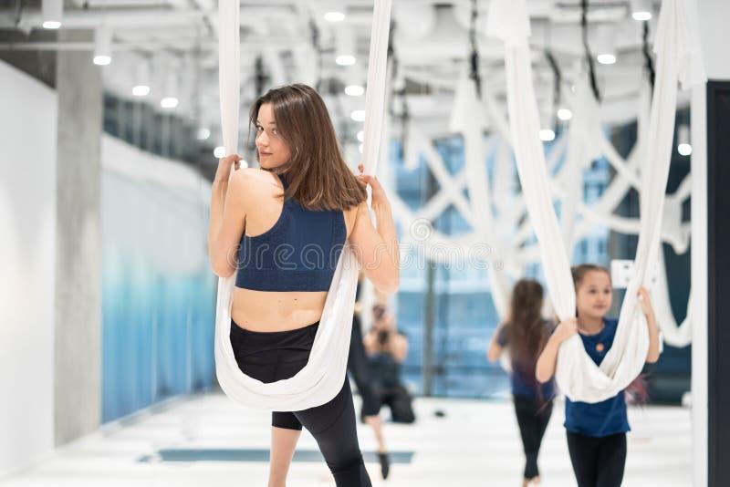 Йога мухы Молодая женщина практикует воздушную антигравитационную йогу стоковые изображения rf