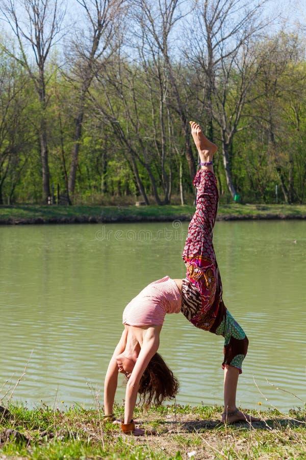 Йога практики молодой женщины на открытом воздухе концепции образа жизни озера съемкой тела здоровой полной стоковая фотография rf