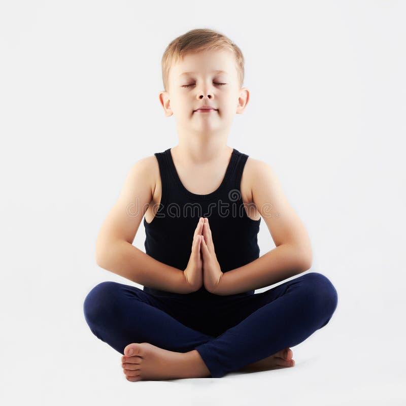 Йога привлекательного ребенка практикуя мальчик делает йогу стоковое фото rf