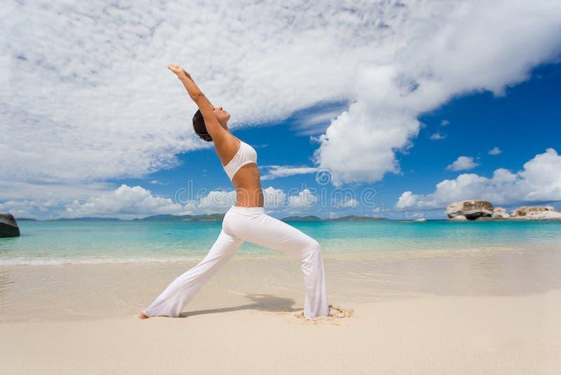 йога простирания пляжа женская Стоковое Фото
