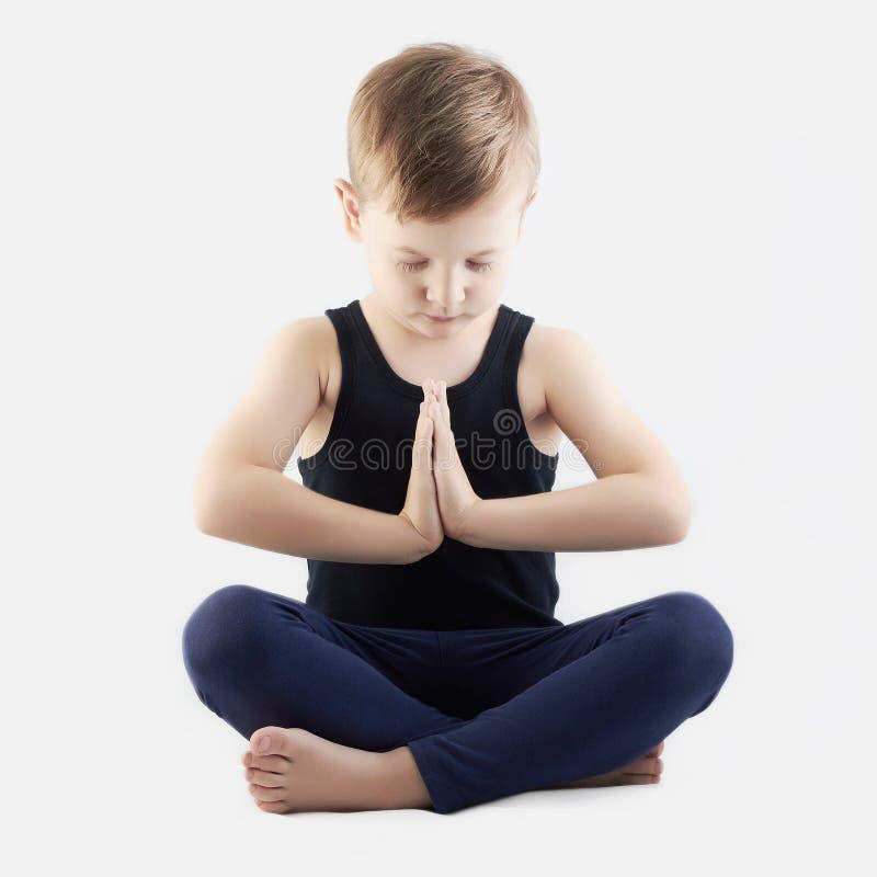 Йога ребенка практикуя мальчик делает йогу стоковое изображение rf