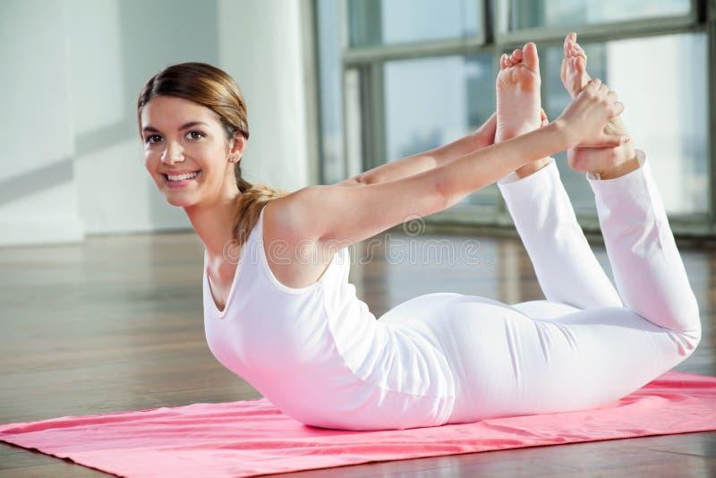 Йога счастливой женщины практикуя стоковое изображение