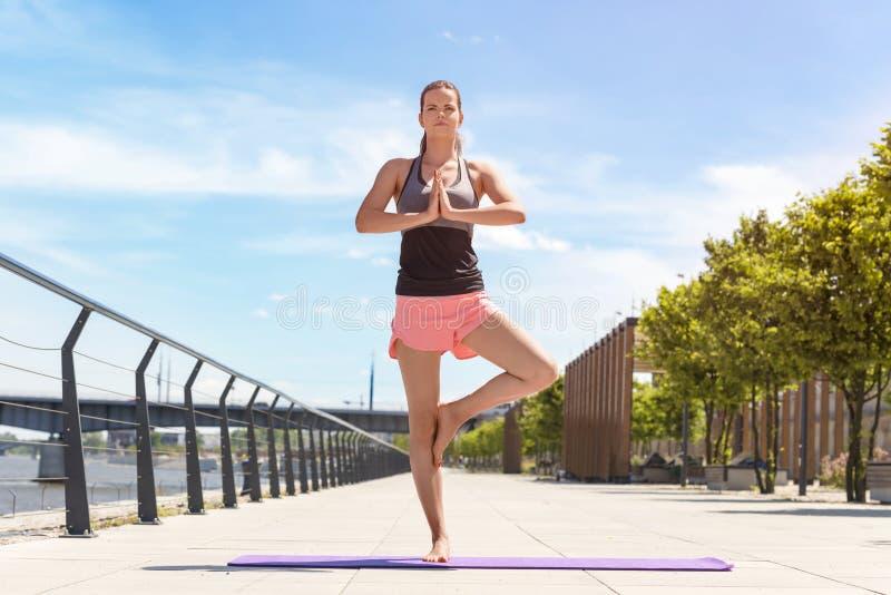 Йога тренировки молодой женщины в руках города поднимает и стоящ на o стоковое фото rf