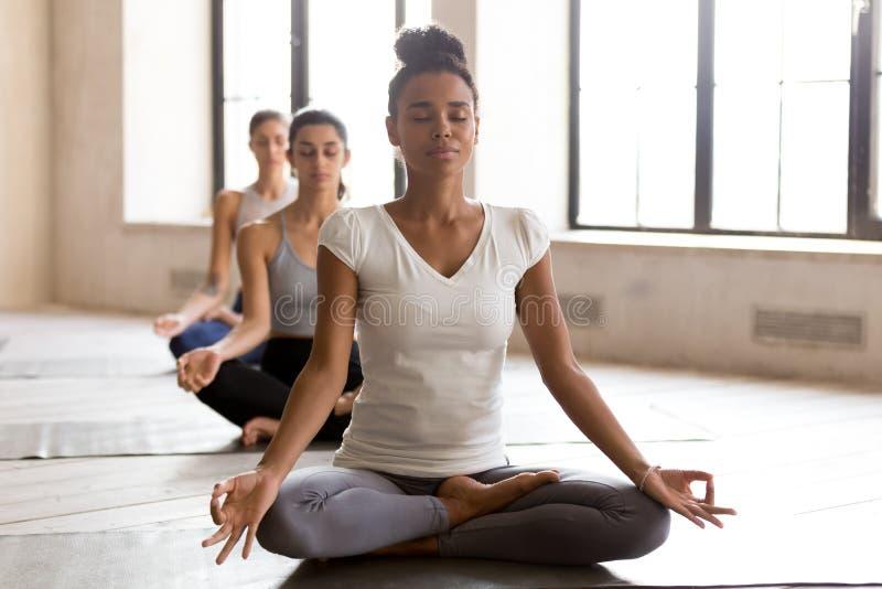 Йога чернокожей женщины и группы Yogi практикуя, делая Ardha Padmasan стоковые фотографии rf