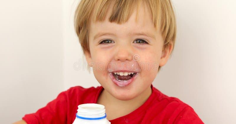 Йогурт радостного ребенка выпивая стоковые фотографии rf