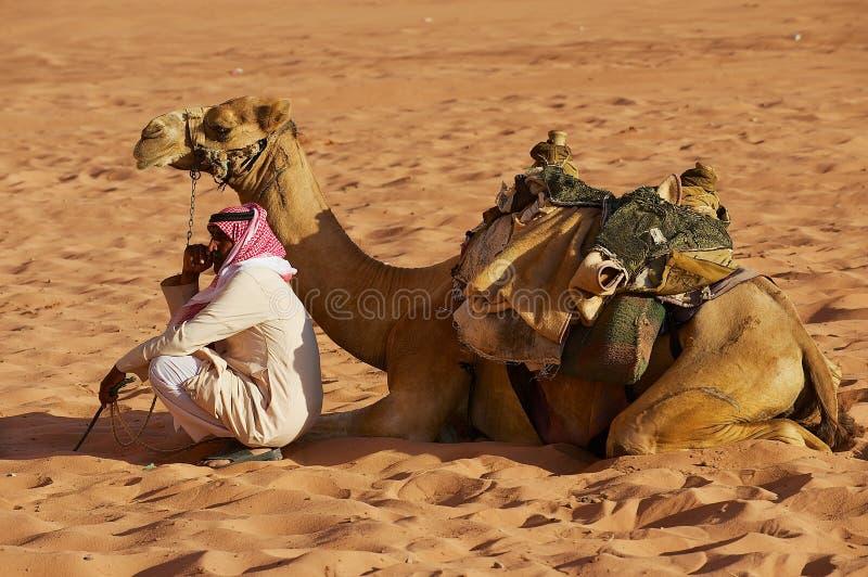 Йорданський человек нося традиционное платье сидит на песке в пустыне рядом с его верблюдом в роме вадей, Джордане стоковые изображения rf