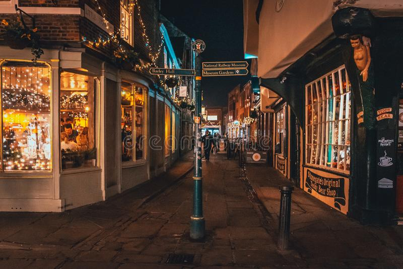 ЙОРК, АНГЛИЯ, 11-ОЕ ДЕКАБРЯ 2018: Люди идя в красивые средневековые улицы города Йорка, Великобритании, окруженной мимо стоковое изображение