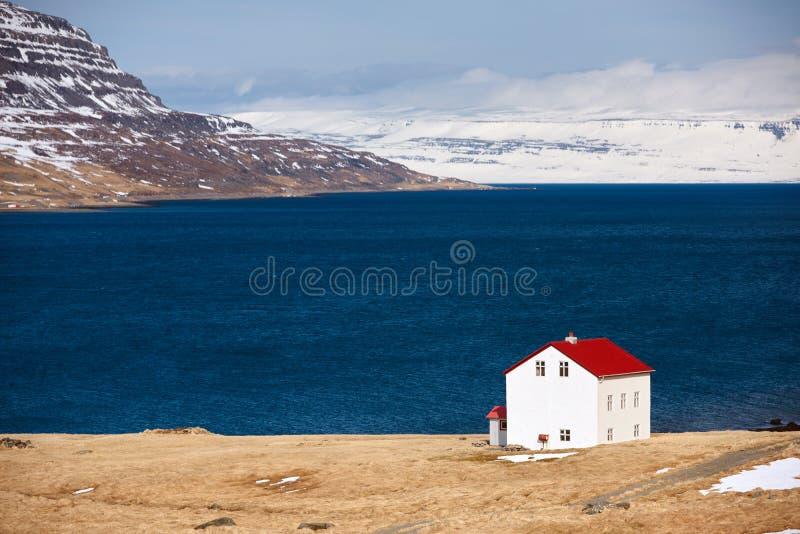 Кабина около гор озера и snowcapped westfjords исландских стоковое изображение rf