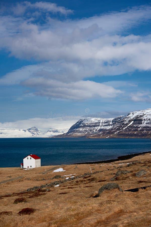 Кабина около гор озера и snowcapped westfjords исландских стоковые изображения