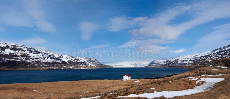 Кабина около гор озера и snowcapped westfjords исландских стоковое изображение