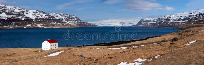 Кабина около гор озера и snowcapped westfjords исландских стоковые фото