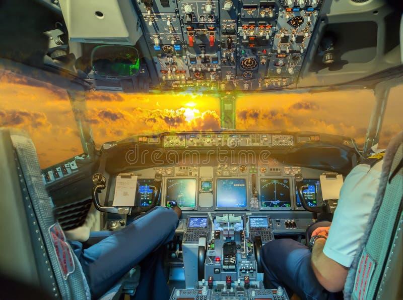 Кабина экипажа арены самолета аэробуса в заходе солнца стоковое фото