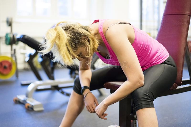 Кавказская белокурая скандинавская тренировка девушки фитнеса на вымотанный отдыхать спортзала стоковые фотографии rf