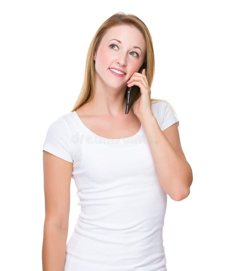 Кавказская беседа женщины к мобильному телефону стоковые изображения rf