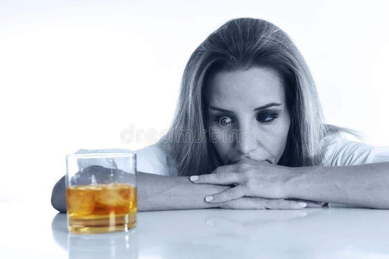 Кавказская белокурая расточительствованная и отжатая спиртная женщина выпивая пьяное шотландского вискиа стеклянное грязное стоковая фотография rf