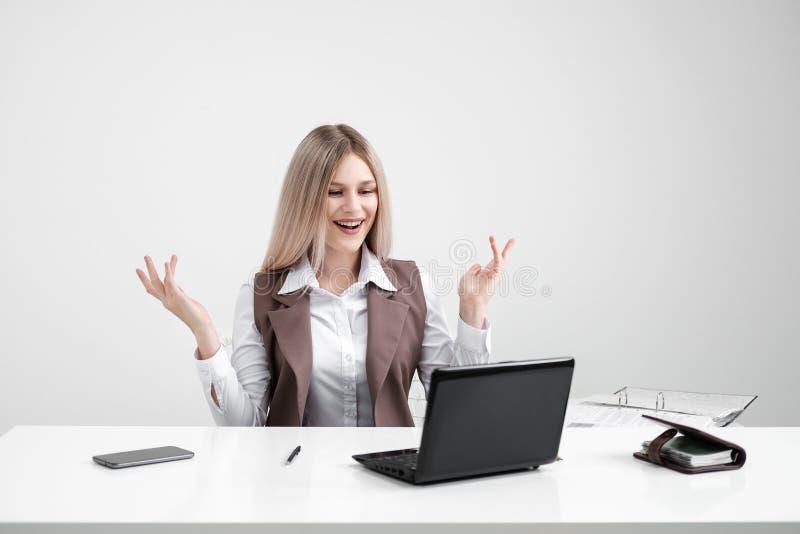 Кавказская девушка сидя на таблице на компьютере в офисе Радуется и усмехается стоковые фотографии rf