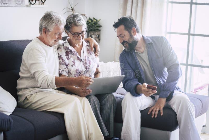Кавказская достигшая возраста семья дома зреют и люди среднего возраста совместно используя приборы технологии как ноутбук и моби стоковое изображение