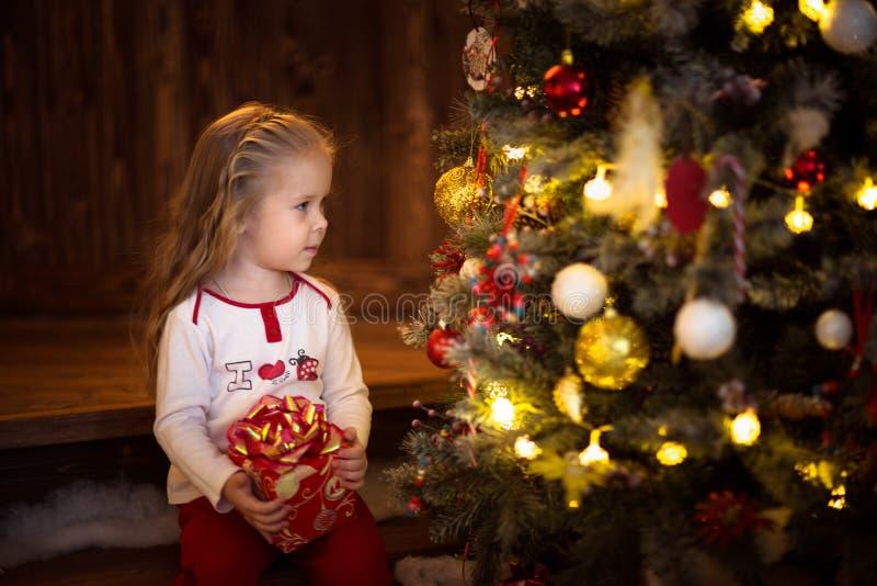 Кавказская девушка с белокурым длинным подарком рождества волос, темными светами стоковые изображения rf