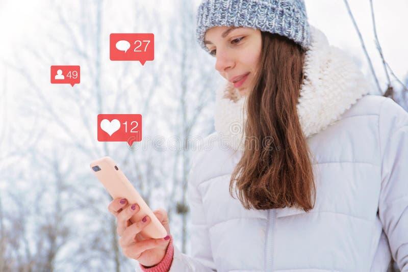 Кавказская женщина девушки держит средства массовой информации instagram телефона социальные следующие значка bloger любят концеп стоковые фотографии rf