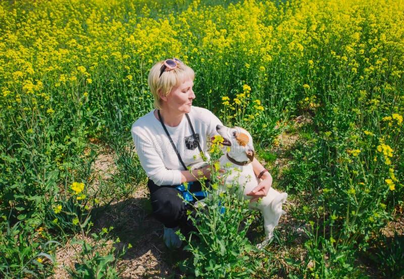 Кавказская женщина играя с ее собакой в траве стоковое фото rf