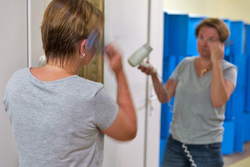 Кавказская женщина кладет волосы при запачканный фен для волос, стоковые фотографии rf